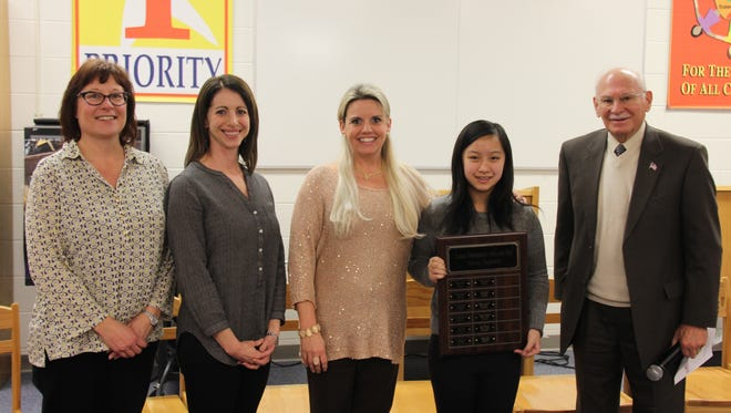 Stevenson Middle School spelling bee winner Vivian Le Tran. The seventh-grader received her plaque from Principal Sheri Grove (center) and event namesake Earl Chorbagian.