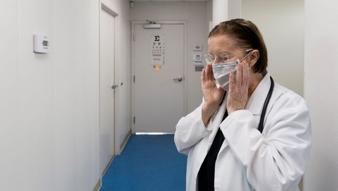 Nurse practitioner Patricia Smith puts on a mask before seeing a patient on Monday, March 5, 2018 at the UrgentCareTravel clinic at Strawberry Plains Pike. Smith is motivated to make a difference to her patients, especially those in the trucking industry, where long hours, sedentary lifestyle, and rigors of the job can lead to a higher incidence of chronic health problems.