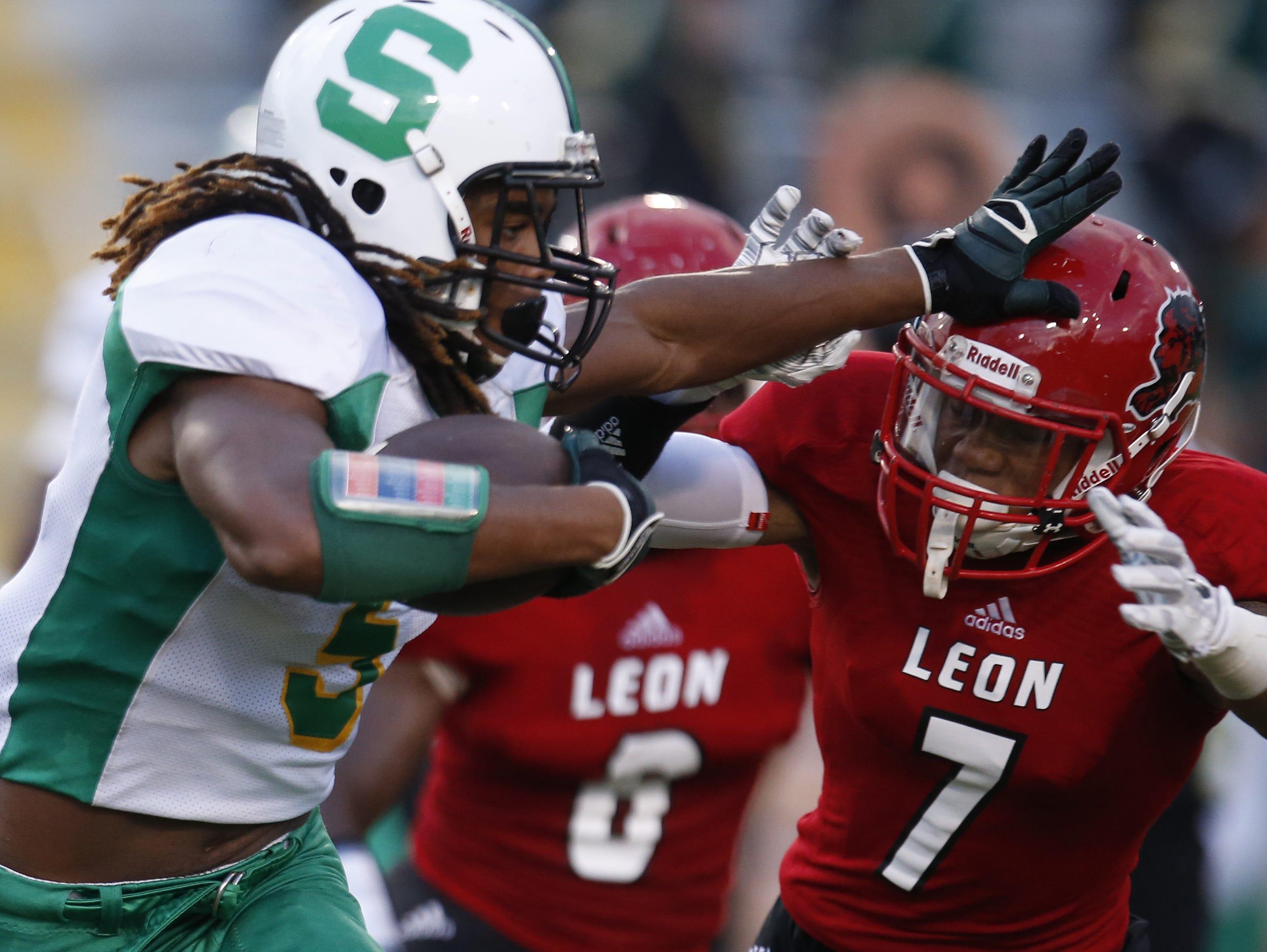 Suwannee's Aaron McAllister stiff arms Leon's Damien Crumitie during their game at Cox Stadium on Friday.