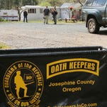 In this photo taken Tuesday, April 14, 2015, an Oath Keepers, constitutional activists, sign marks the entrance to a property on Camp Joy Road near Merlin, Ore, while armed Oath Keepers security guards hover in the background. The site is a gathering of people who support the rights of miners on a claim near Galice, Oregon, that the Bureau of Land Management wants to bring into compliance or shut down. (Timothy Bullard/The Daily Courier via AP)