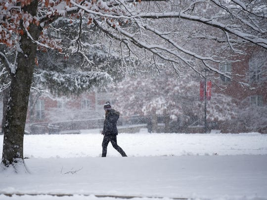 A student walks in the falling snow Dec. 13, 2016, at Earlham College in Richmond.