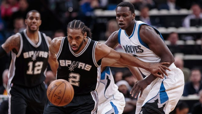 Spurs forward Kawhi Leonard (2) and Timberwolves center Gorgui Dieng, right, chase a loose ball during the first quarter at Target Center in Minneapolis.
