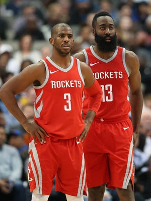 Chris Paul and James Harden look on during a break in the action.