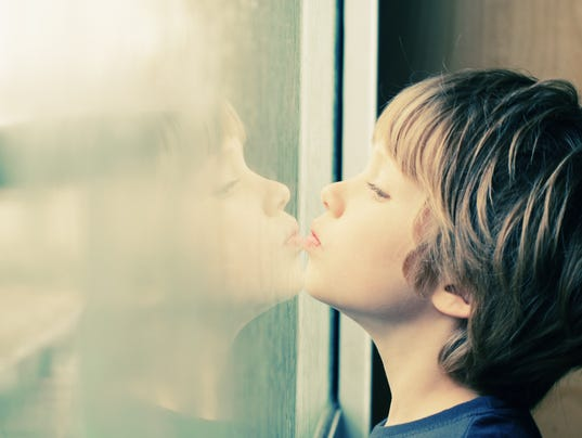 Cute boy looking through the window