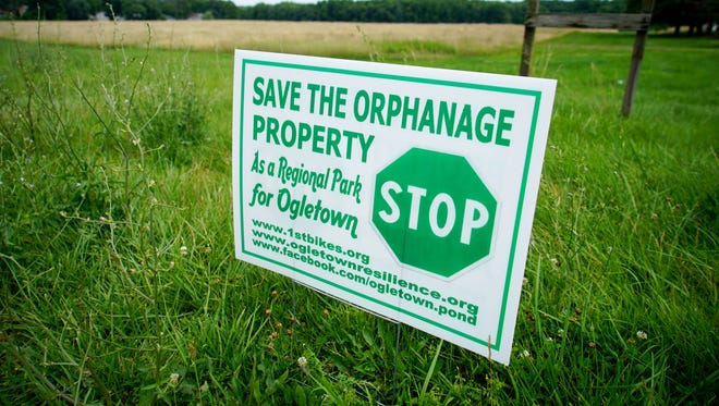 A preservation group that has been pushing local officials to purchase most of the 182-acre property that was once Our Lady of Grace Home for Children put up a sign along the property to gain support.
