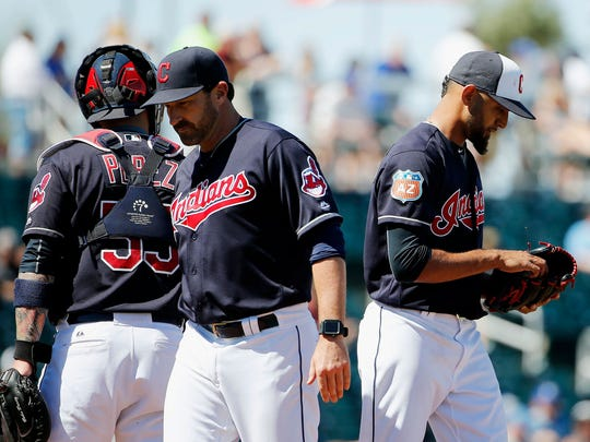 Cleveland Indians pitching coach Mickey Callaway, middle, heads back to the dugout after talking with pitcher Danny Salazar, right, and catcher Roberto Perez, left, during the third inning of a spring training baseball game against the Kansas City Royals Wednesday, March 23, 2016, in Goodyear, Ariz. (AP Photo/Ross D. Franklin)