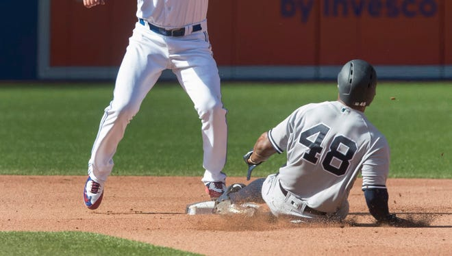 New York Yankees Eric Young Jr. safely steals second base as Toronto Blue Jays shortstop Troy Tulowitzki waits for the throw from home in the seventh inning of their baseball game in Toronto, Sunday Sept. 25, 2016.