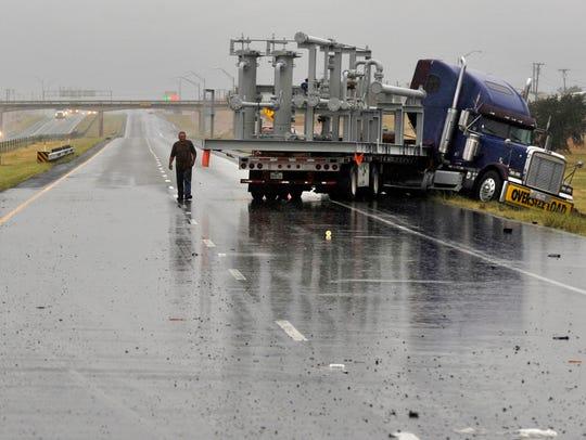 A jackknifed 18-wheeler and a trailer rest on both