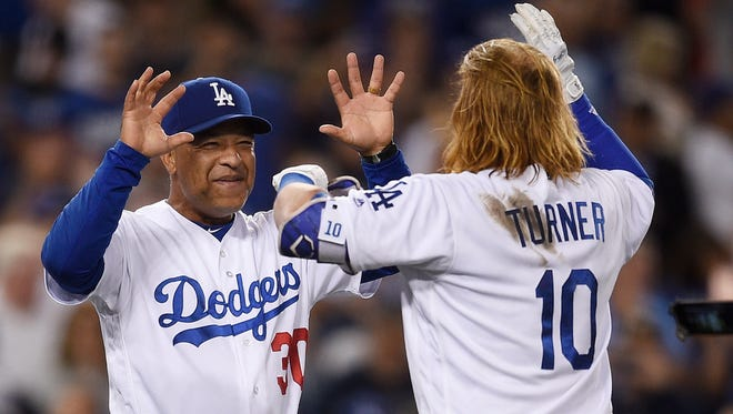 Los Angeles Dodgers manager Dave Roberts, left, celebrates a walk-off single with Justin Turner (10) after a baseball game against the Minnesota Twins in Los Angeles, Wednesday, July 26. The Dodgers won 6-5.