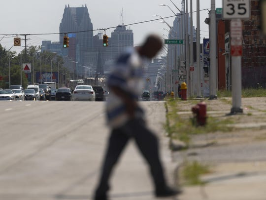 "A pedestrian crosses Gratiot Avenue in Rep. Rashida Tlaib's, D-Mich., 13th district in Detroit, Monday, July 15, 2019. Injecting race into his criticism of liberal Democrats, President Donald Trump said four congresswomen of color, including Tlaib, should go back to the ""broken and crime infested"" countries they came from, ignoring the fact that all of the women are American citizens and three were born in the U.S. (AP Photo/Paul Sancya)"