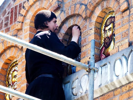Father Tarsizios works on the mosaics at St. George