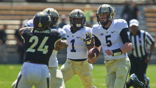 Purdue quarterback Danny Etling looks for room against the black team during the annual spring game Saturday, April 12, 2014, at Ross-Ade Stadium in West Lafayette.