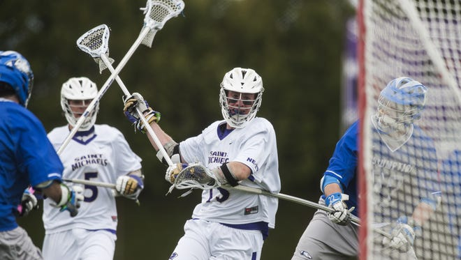 St. Michael's Brian Devilly (15) takes a shot during the men's lacrosse game between the Assumption Greyhounds and the St. Michael's Purple Knights on Saturday afternoon.