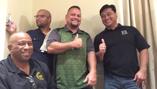 Tony Thompson, seated, principal of Father Duenas Memorial School and president of the Guam Basketball Confederation celebrates the signing of letters of college intent by some of his high school football players April 28 at the Hilton Guam Resort and Spa. Thompson gets thumbs ups from John F. Kennedy football coach Allen Blend, left and Dr. Vince Akimoto.