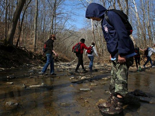Joe Sheffel tests his waterproof boots in a creek at
