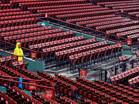 Boston Red Sox usher Kathy Gould, of Boston, stands in the pouring rain while keeping fans away from the seating bowl due to the weather prior to a scheduled baseball game against the Cleveland Indians at Fenway Park, Wednesday, Aug. 2, 2017, in Boston. The game was delayed due to heavy rain and thunderstorms. (AP Photo/Charles Krupa)