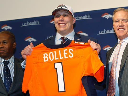 The Denver Broncos' first-round selection in the NFL draft, offensive tackle Garett Bolles, center, holds up his jersey while flanked by head coach Vance Joseph, left, and general manager John Elway during a news conference at the team's headquarters Friday, April 28, 2017, in Englewood, Colo. (AP Photo/David Zalubowski)