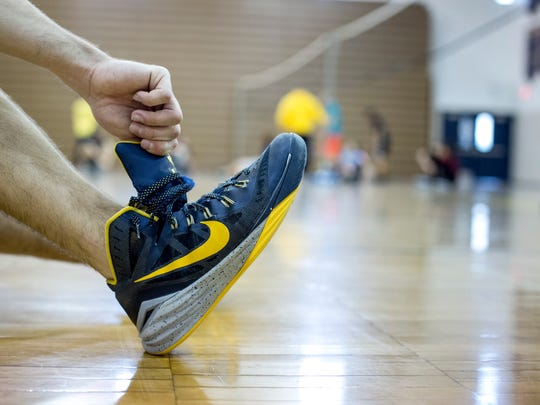 A student ties their shoe during a recreational sports gym class Friday, Feb. 5, 2016 at Port Huron Northern High School. The Fund Our Floor campaign has reached its goal and $120,000 has been raised to replace the 51-year-old wooden gym floor.