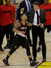 Portland Trail Blazers guard Damian Lillard, foreground, reacts after making a 3-point basket at the end of the third period against the Golden State Warriors in Game 2 of a second-round NBA basketball playoff series in Oakland, Calif., Tuesday, May 3, 2016. (AP Photo/Jeff Chiu)