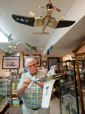 "Dr. James Wheeler holds up one of the model war planes he built as another hangs suspended from the ceiling of his basement ""museum"" of World War II memorabilia in his Tucker Lake Estates home.