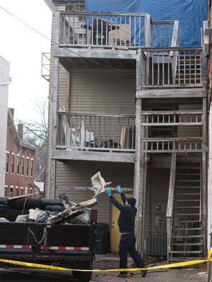 An Employee from Servicemaster Restore throws out a damaged sink from the second-floor apartment at 23 S. Paint St., after a Nov. 22, 2017, fire. The Chillicothe Fire Department called the fire - which began on the exterior stairway - suspicious. A state database shows the cause is unknown but notes is was investigated with an arson model.
