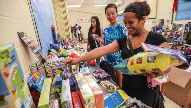 Dededo resident Regina Meno, right, is assisted by a volunteer as she selects six toy items for children in her household during the annual Toy N Joy event at The Salvation Army's headquarters in Tiyan on Friday, Dec. 23, 2016. During this year's campaign, over 8,000 toys were donated, by various local businesses, civic organizations, non-profit groups, public schools and the U.S Marine Corps Reserve Toys for Tots Program in hopes of brightening the Christmas holiday for some of the island's children of needy families, said Corps officer Capt. Kim Stambaugh. Stambaugh estimated about 500 applicants will have enrolled in the program with over 2,400 children receiving toys. Besides the free gifts, food boxes were also given to applicants to take home, she added.