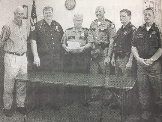 Union County Judge Executive Larry Joe Jenkins, left, signed a proclamation in May 2004 declaring the week of May 15th as Police Week in Union County and May 15th as Police Memorial Day. Also present for the signing were, from left, Morganfield Police Chief Tom Carmon, Sturgis Police Chief Gene Wilson, KSP Public Information officer for Post 16 Mark Applin, UC Deputy Sheriff John Shofner, and Union County Sheriff Mike Thompson.