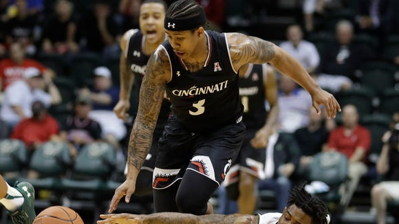 South Florida guard Geno Thorpe (13) reaches for the ball as Cincinnati guard Justin Jenifer (3) drives up the court during the second half of an NCAA college basketball game Wednesday, Feb. 15, 2017, in Tampa, Fla. Cincinnati won the game 68-54.
