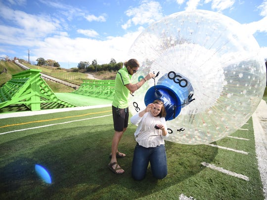 Whitney Good, center, exits a DRYGO ball after riding it downhill at Outdoor Gravity Park in Pigeon Forge on Wednesday, Nov. 4, 2015. The park is now offering dry zorbing alongside it's traditional wet zorbing rides, in which passengers also roll downhill in a plastic sphere, but water added. (ADAM LAU/NEWS SENTINEL)