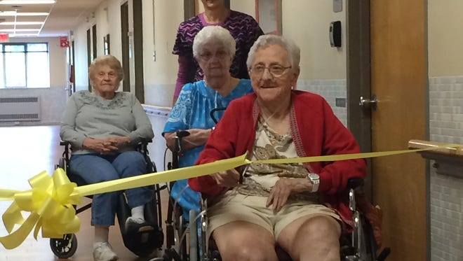 DCMC Skilled Nursing Facility resident Dorothy Schley cuts the ribbon to officially open the renovated facility on Wednesday, Aug. 24.