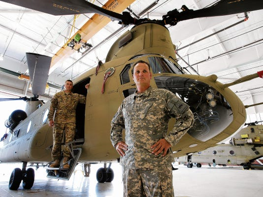 Chief Warrant Officer 3 Landon Dykes, foreground, and Chief Warrant Officer 4 Ryan Dechent show the new Chinook helicopter at Bravo Company, 2nd Battalion, 501st Aviation Regiment at Fort Bliss. The unit is the first in the Army to receive the new version of the helicopter.