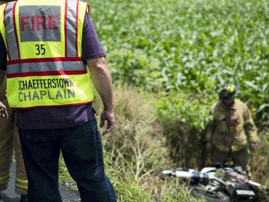 The Rev. Dan Donmoyer, chaplain for Schaefferstown Fire Co., watches from the road as crews investigate the scene of a fatal motorcycle accident in the 700 block of Route 419 in Heidelberg Township on Tuesday.