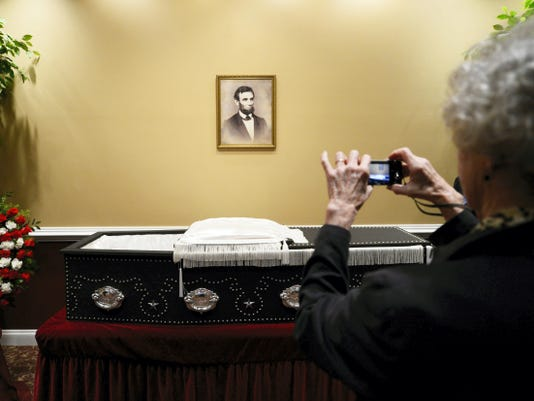 Donna Smeltzer of Hanover takes a photograph Tuesday of a replica of Abraham Lincoln's coffin on display at Heffner Funeral Chapel & Crematory.