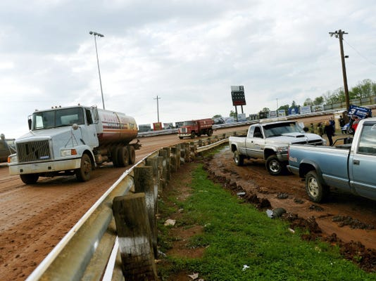 Williams Grove Speedway trucks groom the wet track after torrential rain hit the track before a World of Outlaws race in 2014. Dirt-track owners often wrestle with the decision to cancel racing because of the weather.