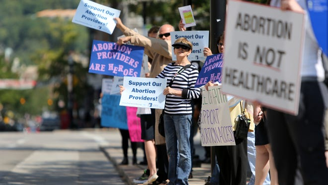 Anti- and pro-abortion advocates protest on Aug. 15, 2014, in front of the Hamilton County Courthouse in downtown Cincinnati. The protesters were waiting to hear a decision that eventually led to the closure of an abortion clinic in Sharonville.  The Enquirer/ Liz Dufour