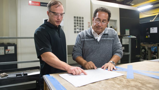 The vice president of Advanced Machine & Tool, Kurtis Riley, (left) works with the company's general manager, Jerry Jacques, in Fort Pierce. The company recently earned a contract from NASA to work on a launch tower at Cape Canaveral.