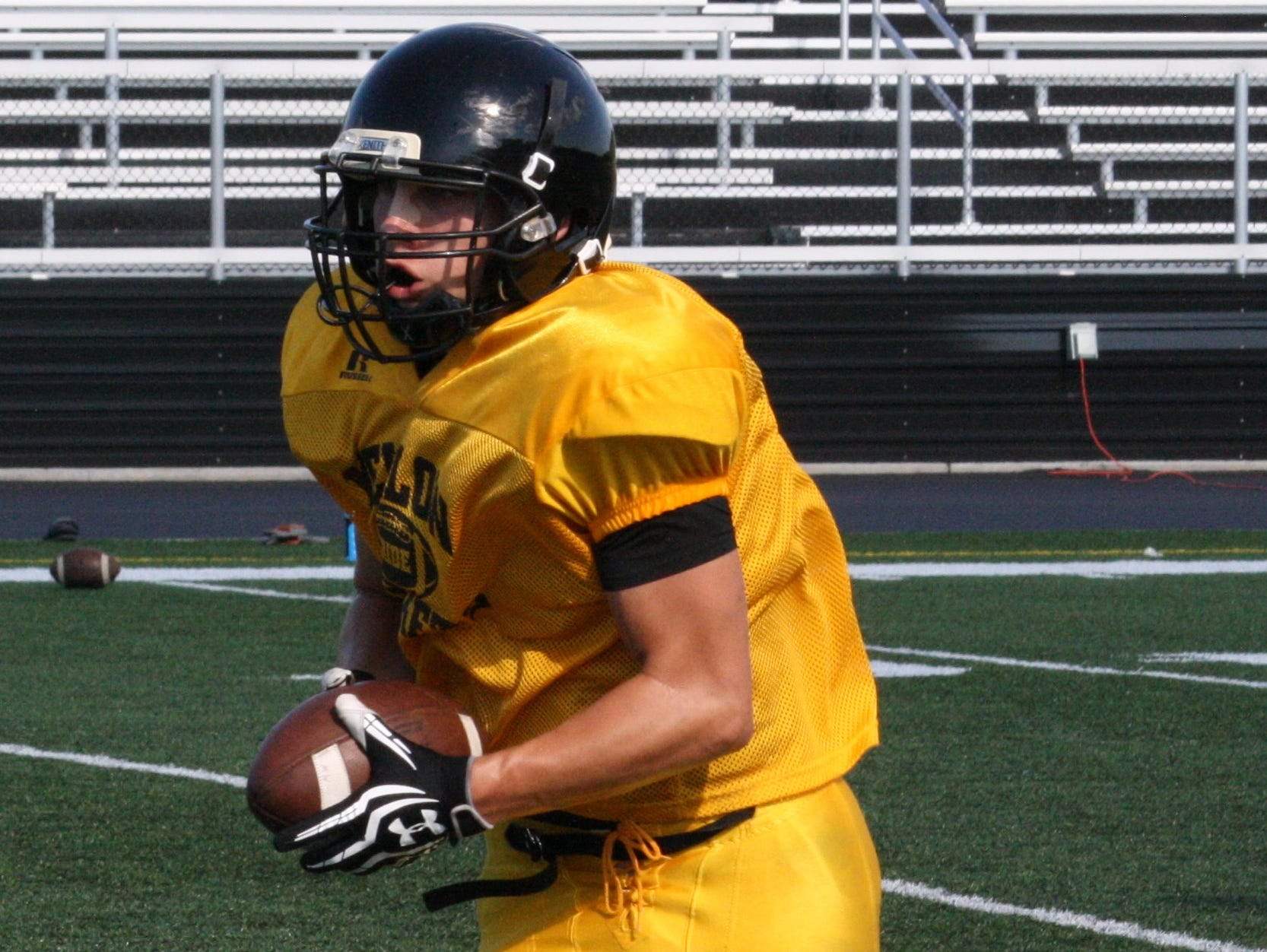 Taylor High School senior running back Koty Kendall carries the ball up field during practice Aug. 13.