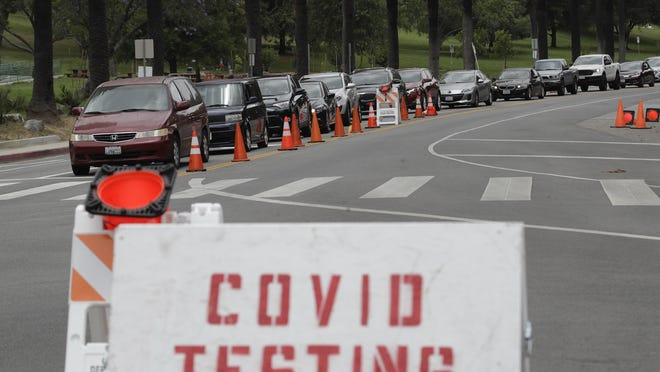 Motorists line up at a coronavirus testing site at Dodger Stadium Monday, June 29, 2020, in Los Angeles. California began reporting additional coronavirus cases to the public Tuesday, Aug. 11, 2020, a week after state officials acknowledged a data problem in late July had caused nearly 300,000 records not to appear in its health system.