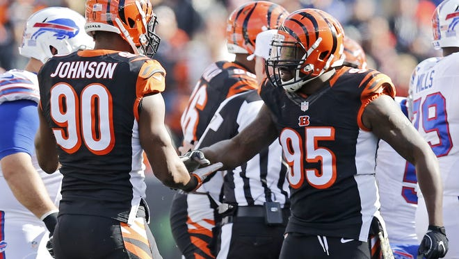 Cincinnati Bengals defensive end Michael Johnson (90) and defensive end Wallace Gilberry (95) celebrate a tackle in the first quarter of the NFL Week 11 game between the Cincinnati Bengals and the Buffalo Bills at Paul Brown Stadium in Cincinnati on Sunday, Nov. 20, 2016. At halftime the Bengals led 12-10.