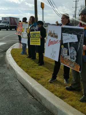 Protesters hold signs at the intersection of Kings Highway and Gills Neck Road on Tuesday, Dec. 27 over the building of a shopping center that they say is on Native American burial ground on the National Historic Register.