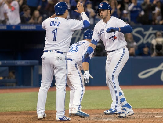 Toronto Blue Jays' Justin Smoak, right, is greeted at home plate by Aledmys Diaz and Russell Martin after he hit a grand slam against the New York Yankees during the eight inning of a baseball game in Toronto on Sunday, April 1, 2018. (Fred Thornhill/The Canadian Press via AP)