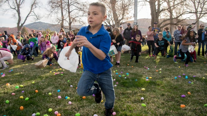 Kage Maddon, 8, sprints away from the crowd at the 31st annual Easter egg hunt at Main Street Park in Cedar City Saturday, March 31, 2018. 30,000 eggs were strewn about the park, and all were collected in less than three minutes.
