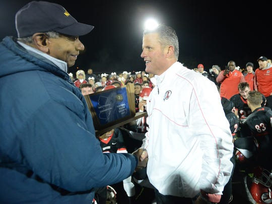 Lenape head coach Tim McAneney receives the South Jersey Group 5 sectional trophy after a 10-7 win over Rancocas Valley in Saturday night's South Jersey Group 5 championship at Rowan University in Glassboro.