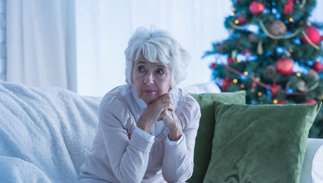 Senior woman sitting alone on sofa, christmas tree in background