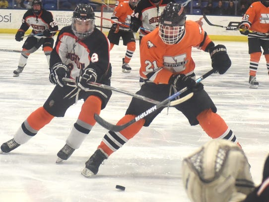 Brighton's Tim Erkkila (left) tries to check Northville's