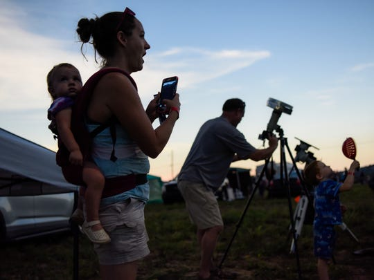 (Left to right) Larissa Glynn, 1, is strapped to Lauren Glynn's back as they excitedly experience the total solar eclipse while Robert Glynn takes photographs to commemorate the day at Orchardale Farm in Cerulean, Ky., on Monday, Aug. 21, 2017. Lauren attended the University of Southern Indiana and lived in Evansville for eight years before moving to Tucson, Arizona, to be close to family in 2009.