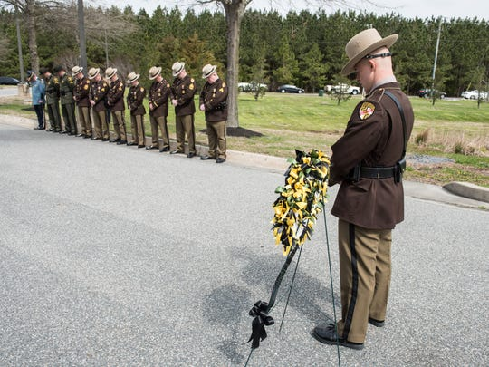 A trooper waits alongside the memorial wreath during the 30th Anniversary Memorial Service for Trooper First Class Eric Monk at the Princess Anne Barrack X in Princess Anne on Monday, April 9, 2018.