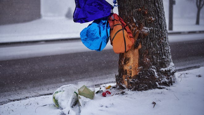 Bouquets of flowers and balloons can be seen Thursday, Feb. 23, 2017, in Sioux Falls alongside a damaged tree where Kareem Hussein Cisse, 15, was killed in a car accident Wednesday morning. Alexander Lingor, 16, the alleged driver of another vehicle involved, was arrested and charged with second-degree murder and manslaughter.