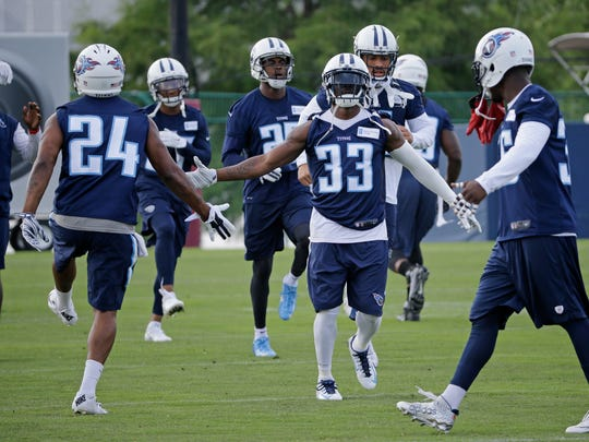Titans cornerbacks Perrish Cox (24) and Brice McCain (33) warm up before practice June 14.