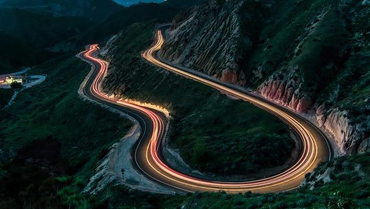 A long exposure creates strands of light as cars wind